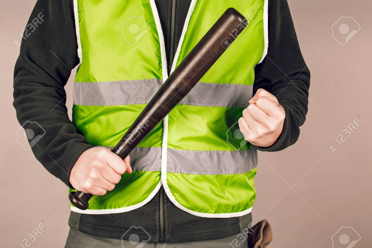 man in a yellow vest, a Builder or a protester with a baseball bat in his hands on a gray background. - 126139635
