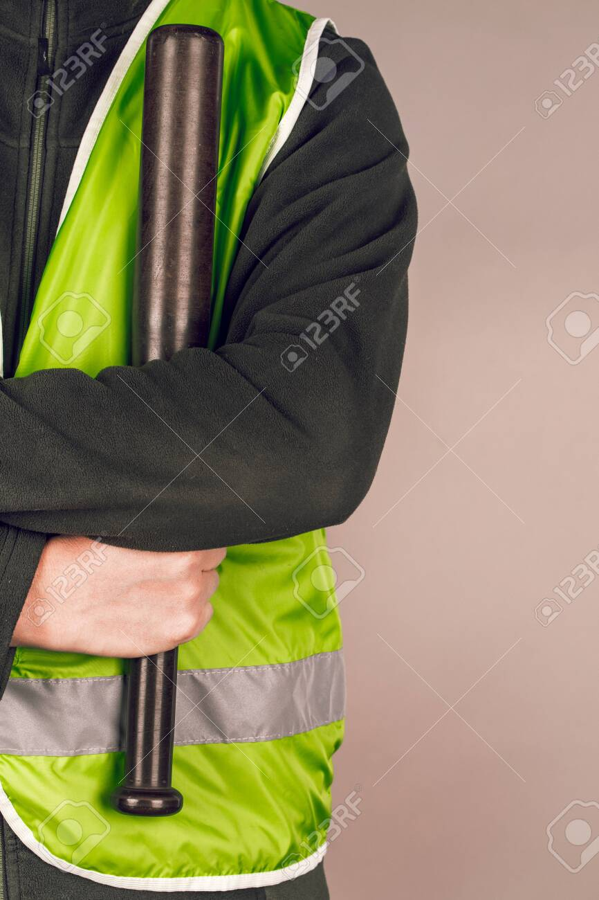 man in a yellow vest, a Builder or a protester with a baseball bat in his hands on a gray background. - 126139907