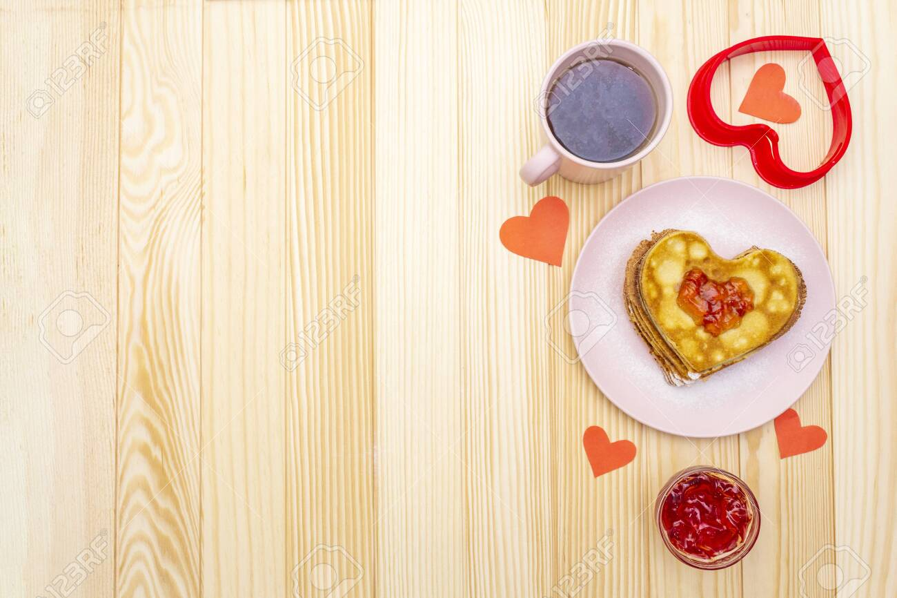 Heart shaped pancakes for romantic breakfast with strawberry jam and black tea. Shrovetide (carnival) concept. On wooden background, top view. - 136827906