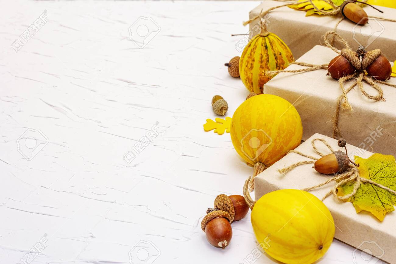 Zero waste gift concept, no plastic life style. Creative autumn decor with paper boxes, mini pumpkins, acorns and fall leaves. Thanksgiving or Halloween concept on white putty background, copy space - 156715734