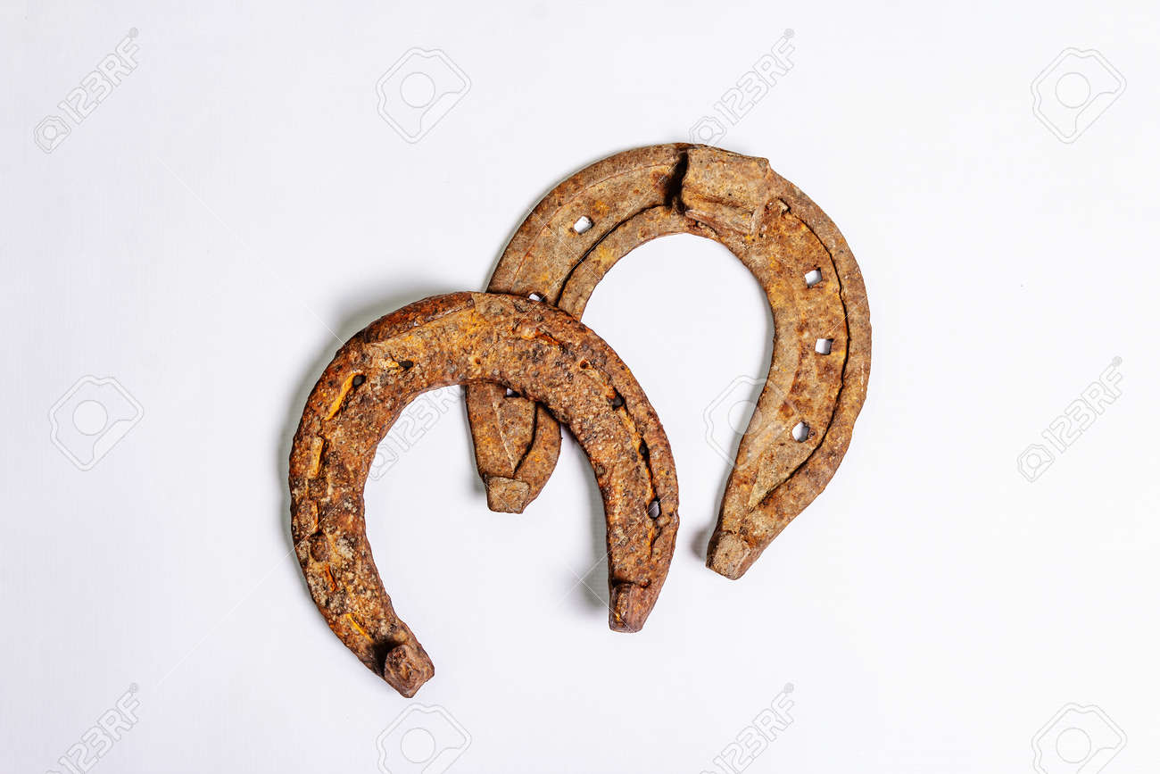 Cast iron metal horseshoes isolated on white background. Good luck symbol, festive concept. Badly worn rusty horse accessories - 162914998