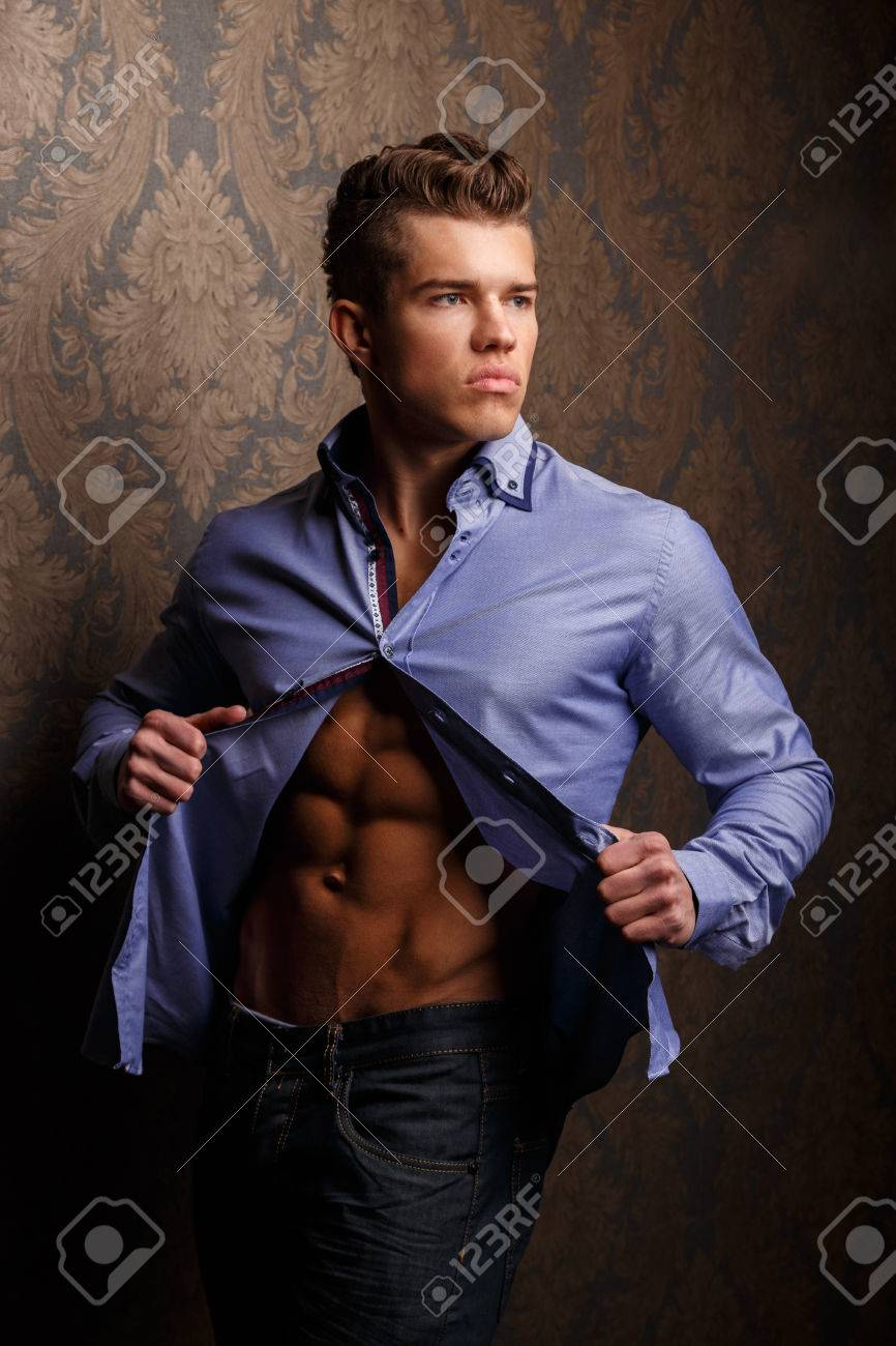fashion portrait of man in shirt showing his abs and poses over