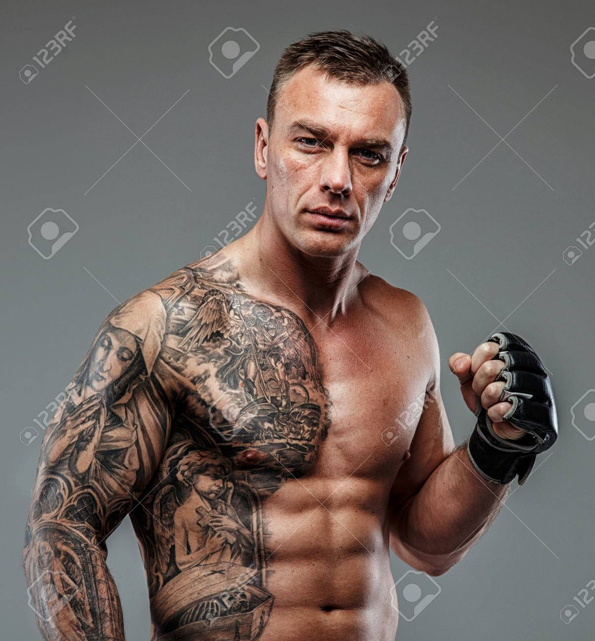 Strong muscular fighter with tattoo poses - 38249048