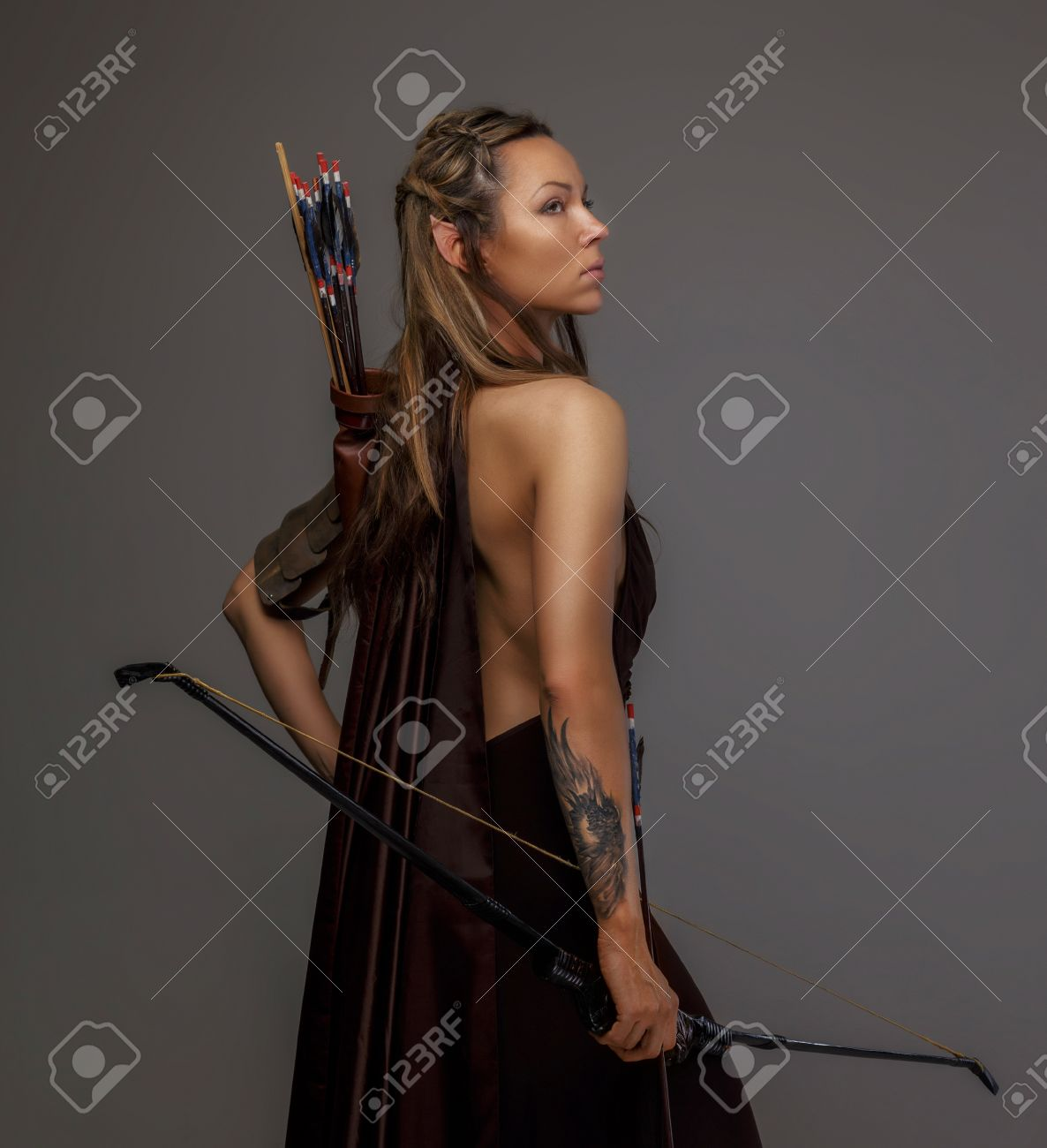 beautiful elf woman with bow in her hand isolated on gray stock