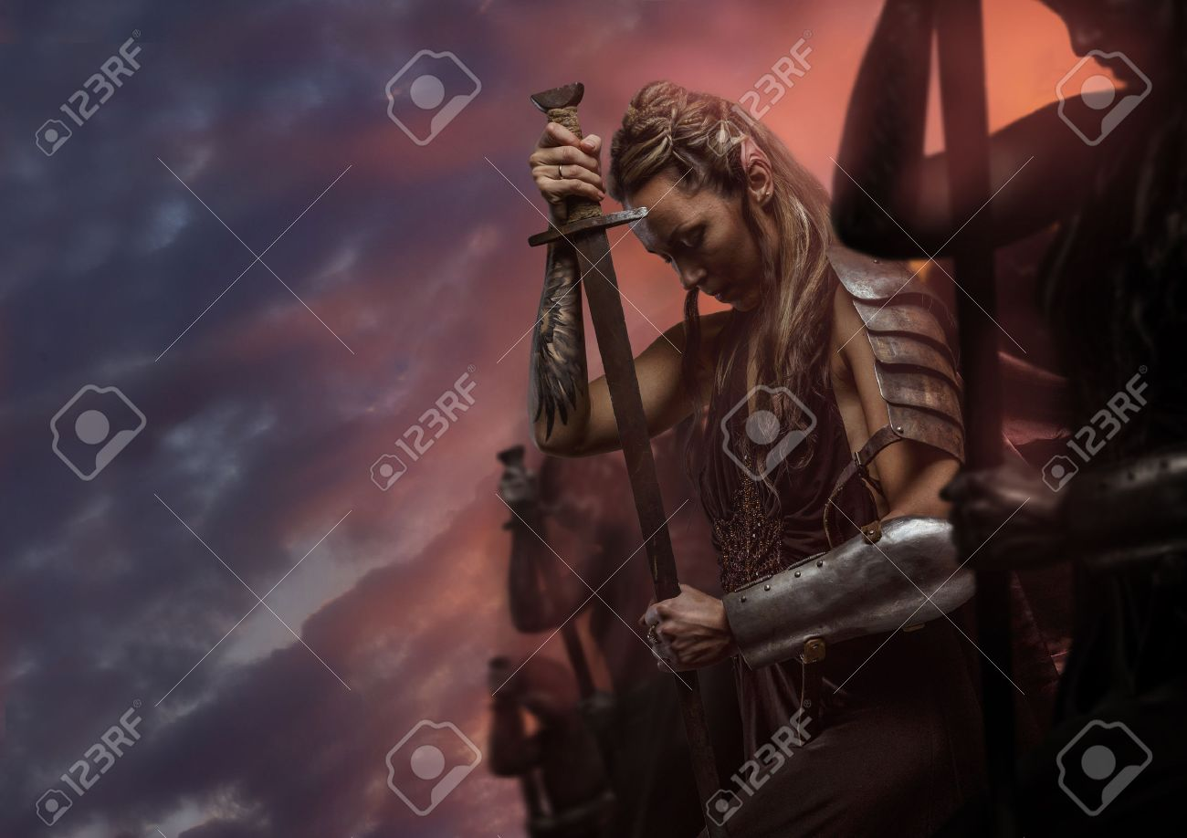 beautiful female warrior elf with sword over cloudy sky stock
