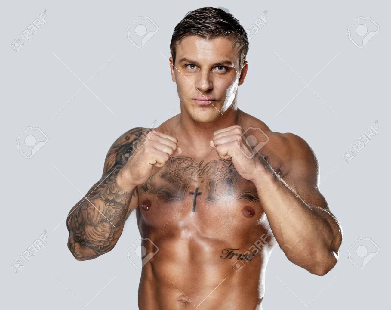 Man with body tattos posing on grey background. Studio shoot. - 40247071