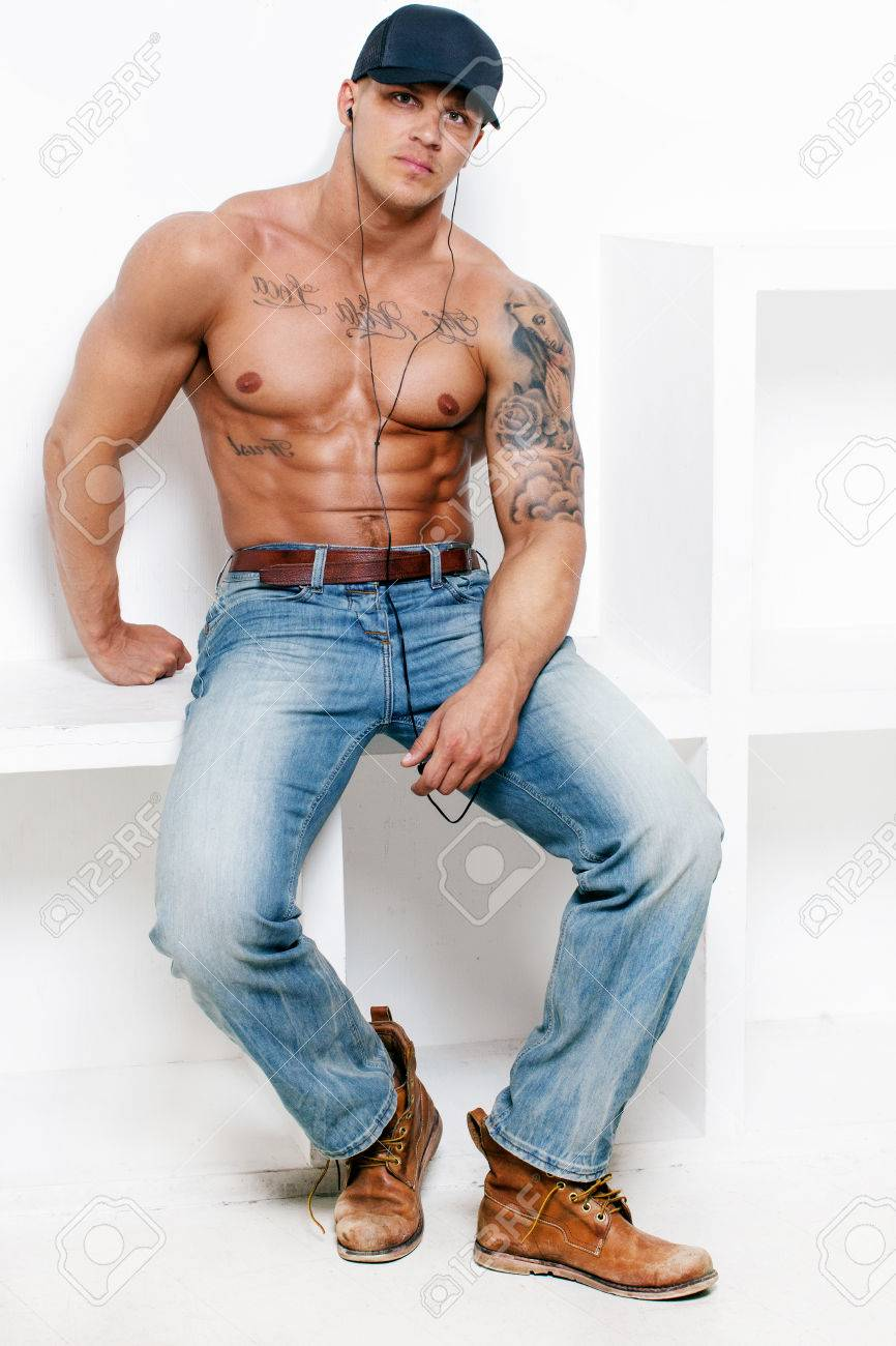 fb0aa27c Awesome muscular guy in blue jeans and a cap on white background Stock  Photo - 40246800