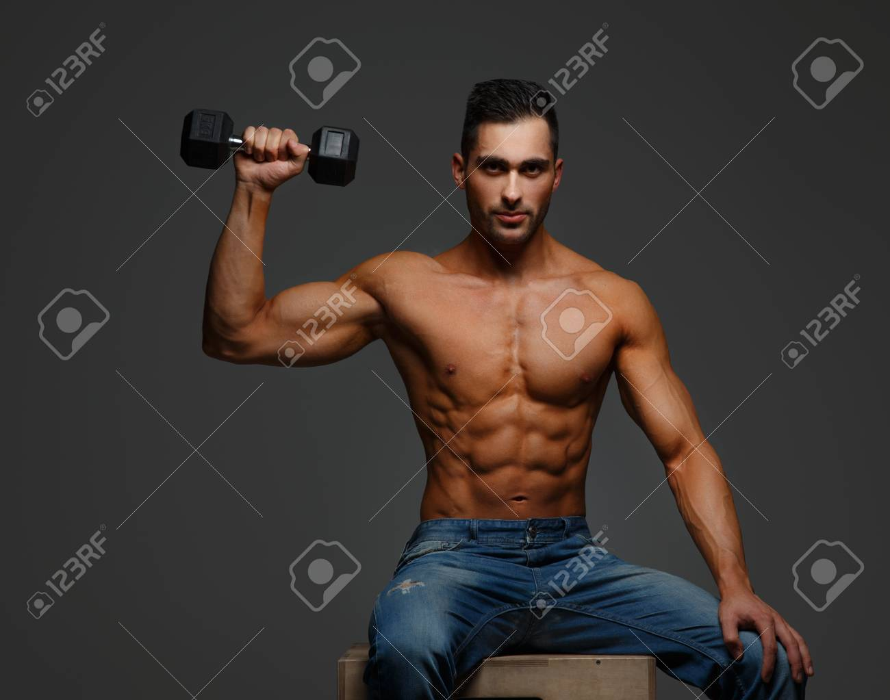 d70a7ddb Shirtless muscular guy in blue jeans holding dumbell. Isolated on grey  background Stock Photo -