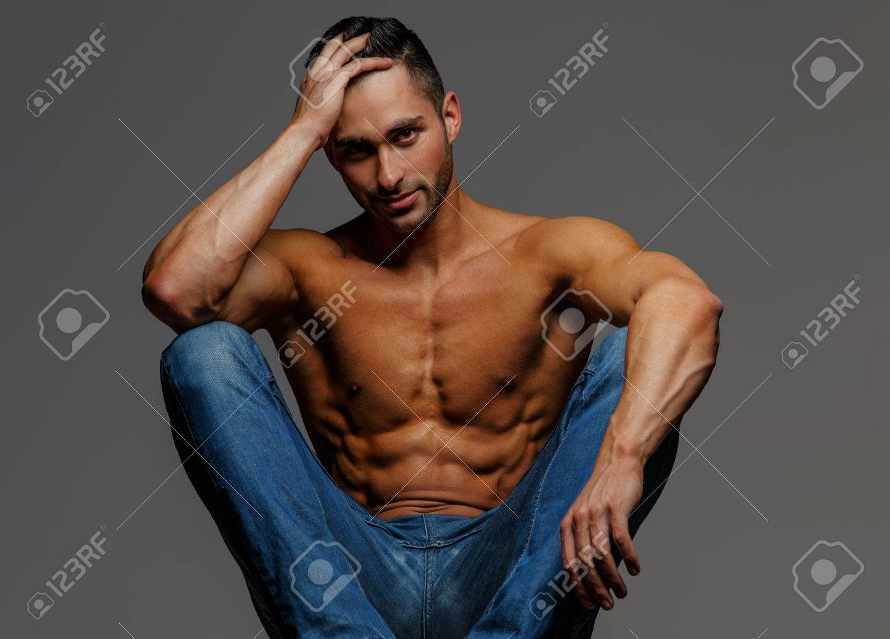 ac7d9f8a Shirtless attractive muscular guy in blue jeans sitting on podium on grey  background Stock Photo -