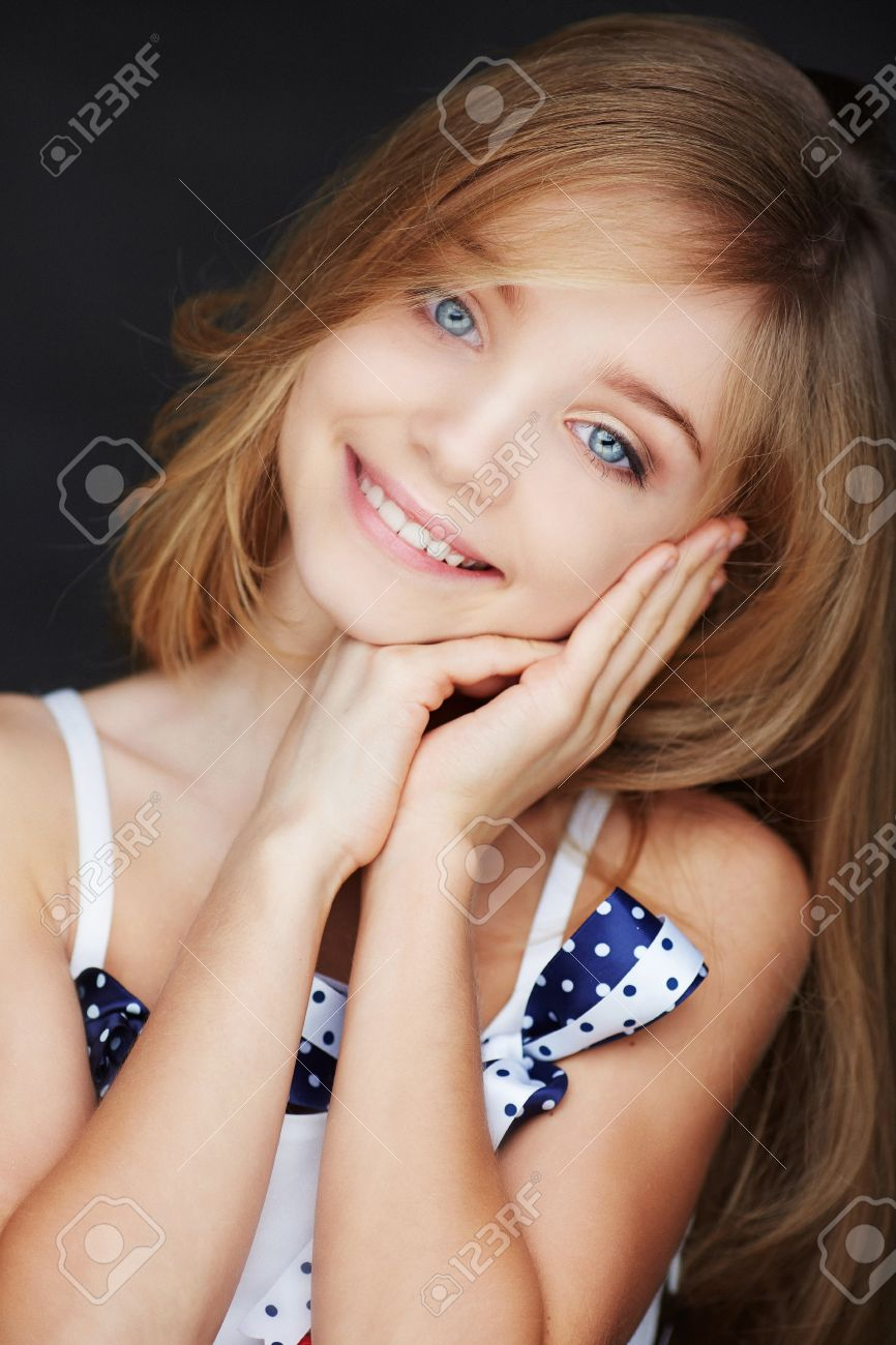 Cute smilling girl with blue eyes. Isolated on dark background. - 41234895