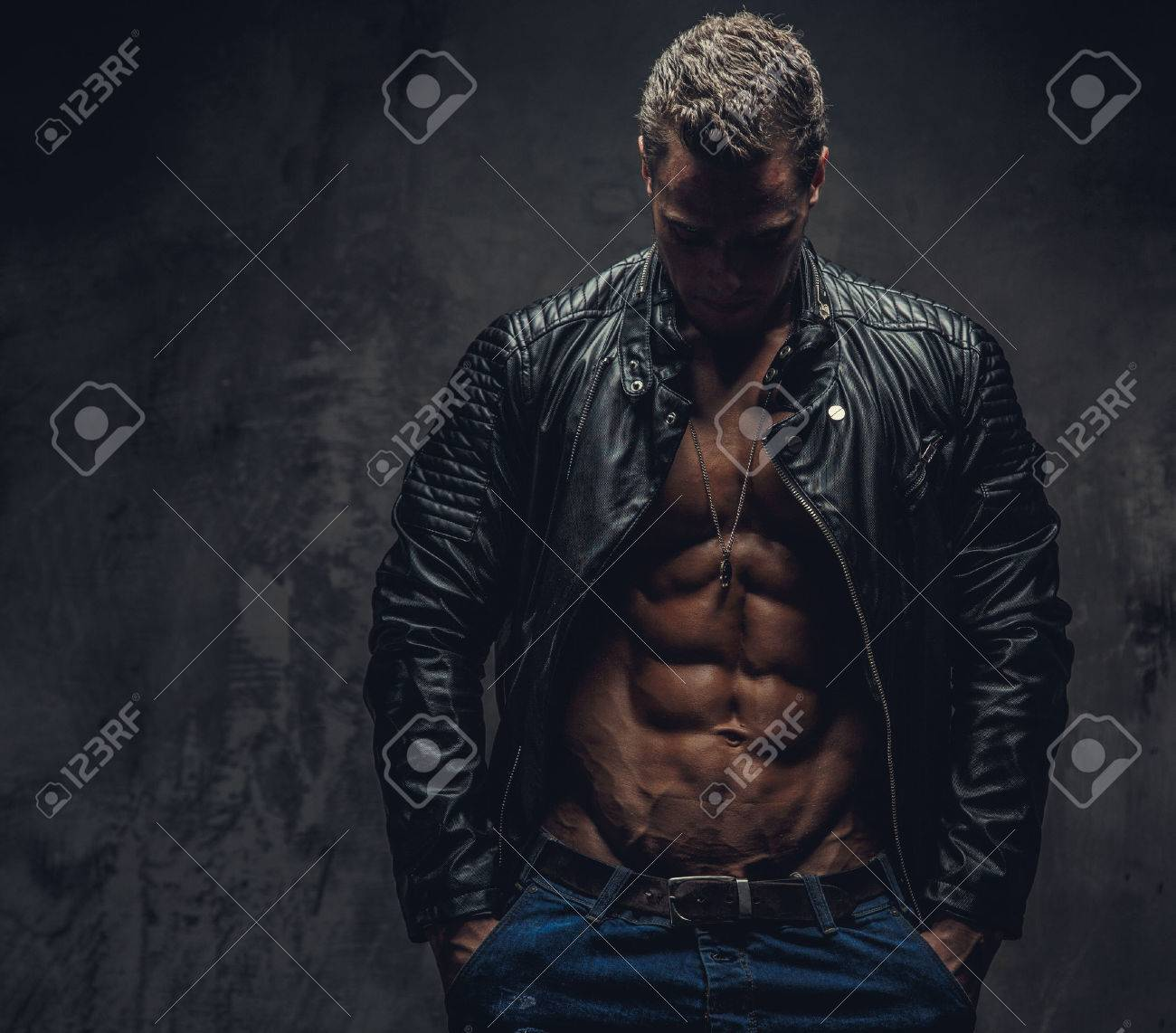 Muscular male in blue jeans and black jacket wearing on shirtless body. Isolated on grey background. - 41238593