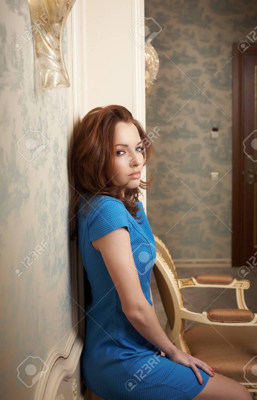 554f55f3c Foto de archivo - Hermosa mujer morena con vestido azul posando cerca de la  pared de antigüedades.