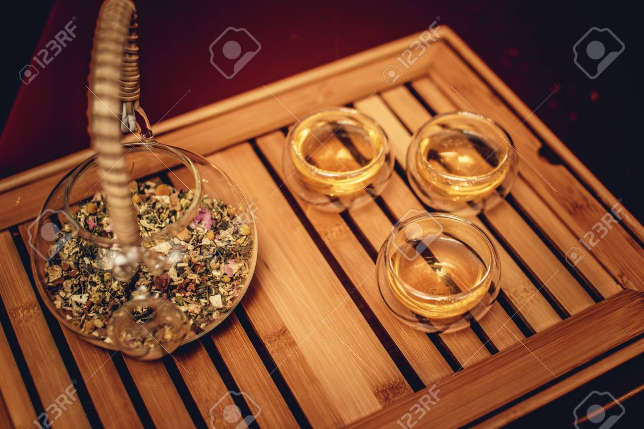 Vassoi In Legno Con Vetro : Teiera cinese con tre tazze di vetro e erbe sul vassoio di legno
