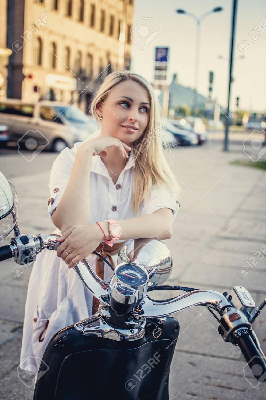 Archivio Fotografico - Femmina con lunghi capelli biondi in abito bianco in  posa vicino a scooter sulla strada in città. 0242d9caea8
