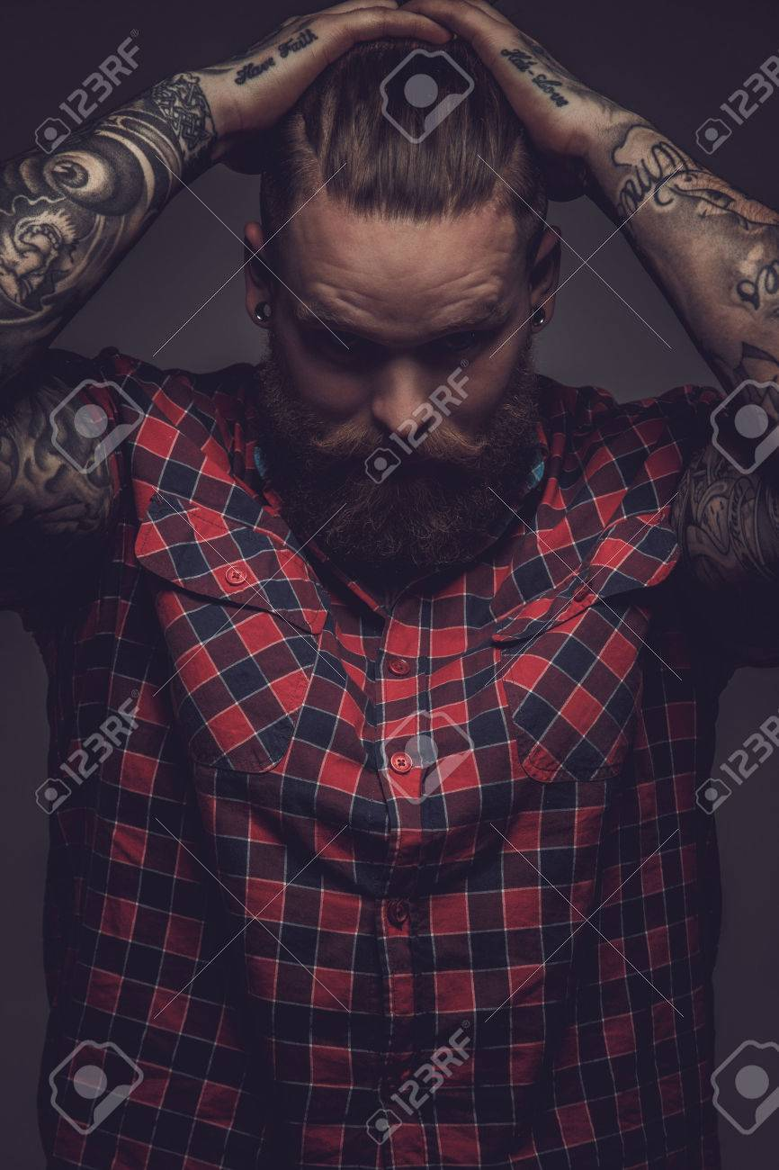 Brutal guy with beard and tattooes holding his head. Isolated on grey background. - 46987637