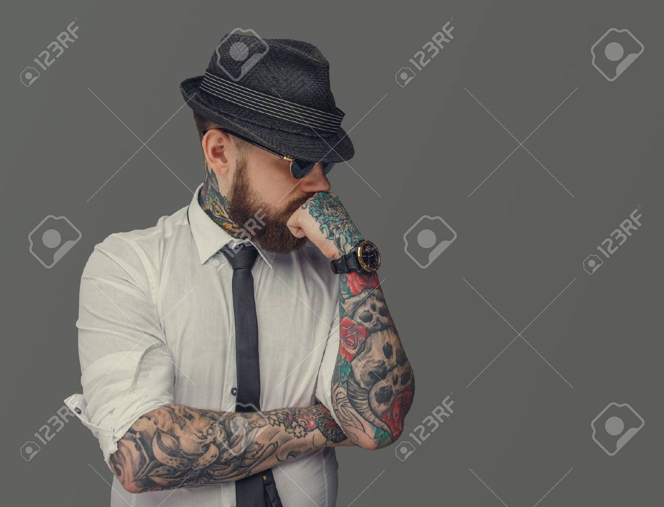 Man with tattooed arms thinking. Isolated on grey background. - 52473110