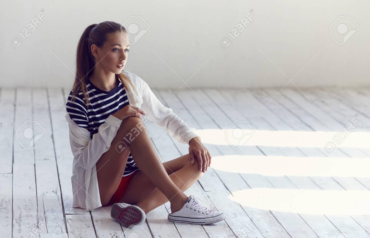 Slim Girls In Black And White Shirt Sitting On White Wooden Floor Stock Photo