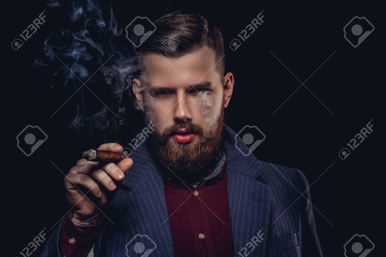Serious bearded man in a suit smoking cigar. - 53660296