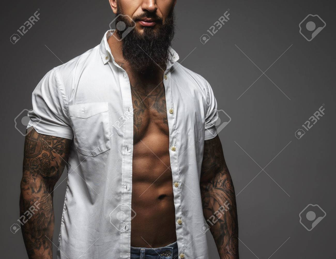 Bearded muscular man in a white shirt isolated on a grey background. - 54362428