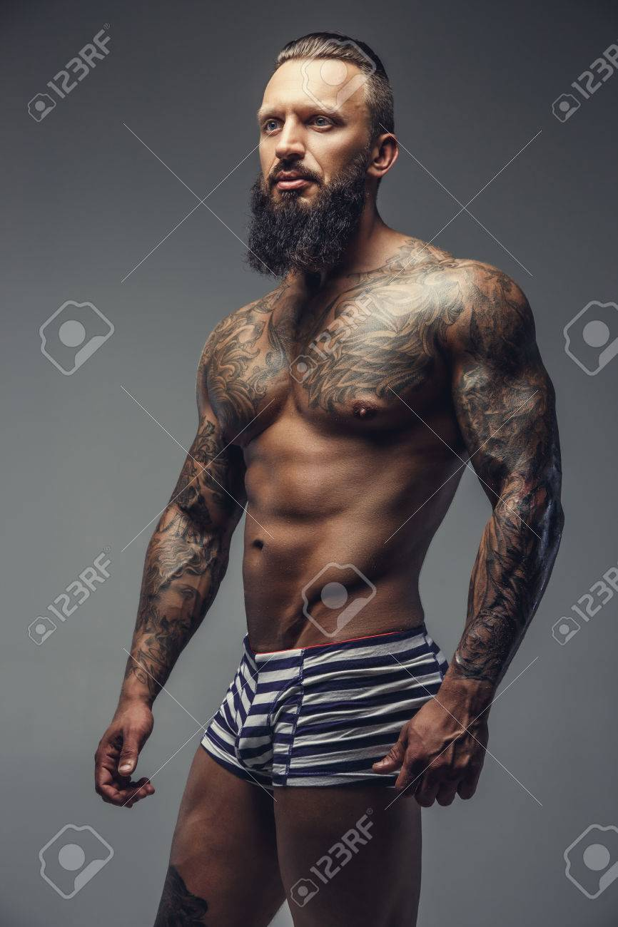 Homme Barbu Nu nu homme barbu avec le corps tatoué debout sur un fond gris. banque