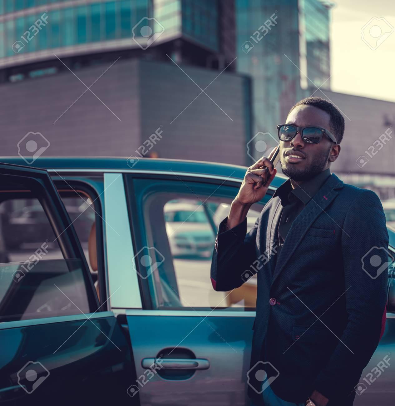 138d4e255e Foto de archivo - Hombre negro en gafas de sol hablando por teléfono  inteligente cerca del coche.