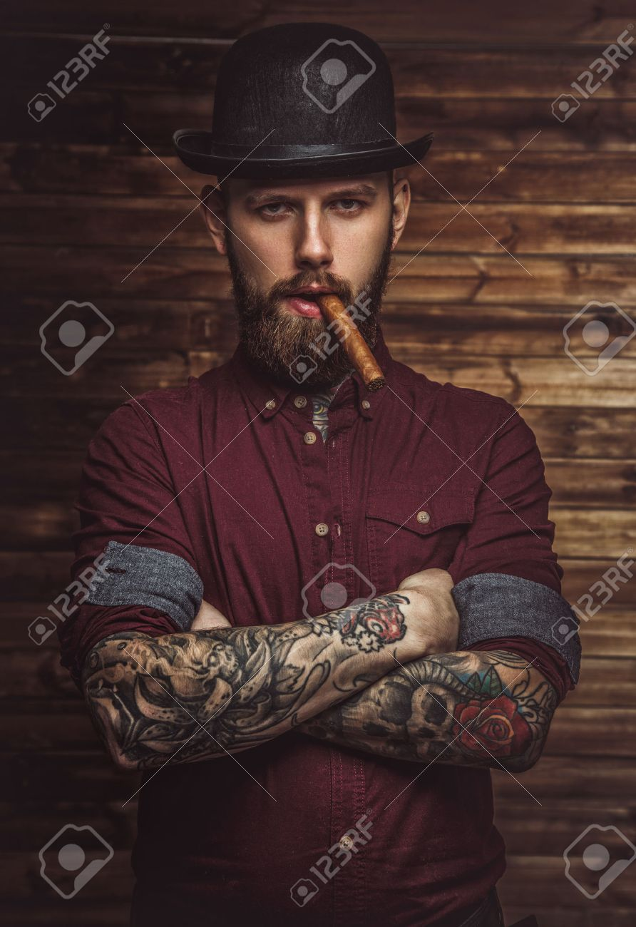 Bearded man with tattooes on arms smoking cigar. - 58123976