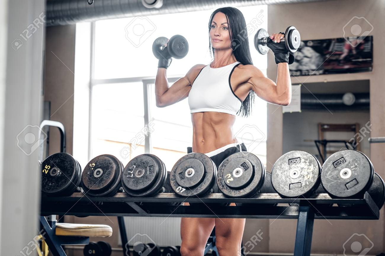 Athletic Female Fitness Model Doing Shoulder Workouts With Dumbbells In A Gym Club Stock Photo