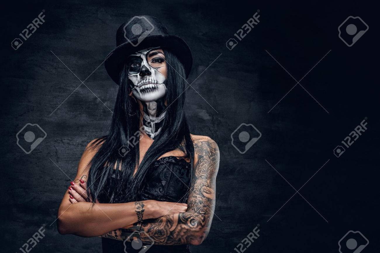 A girl in stylish top hat with skull make up and tattoo on arm. Halloween party. - 65493480