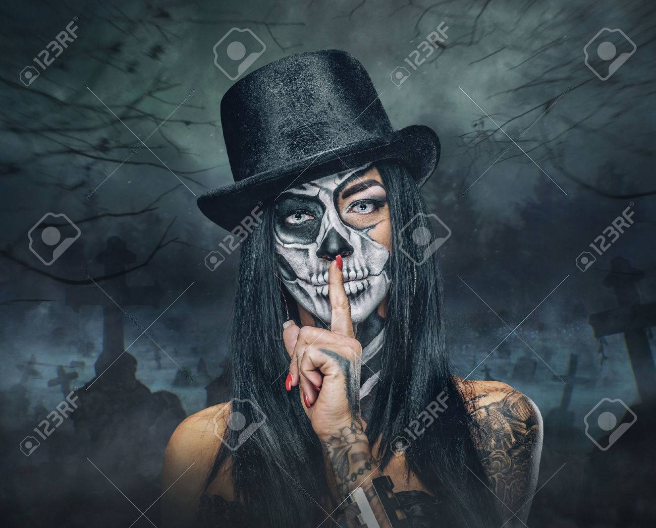 Portrait of female with skull make up in top hat on Halloween. - 65548323