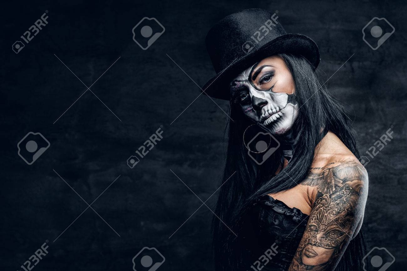A Girl In Stylish Top Hat With Skull Make Up And Tattoo On Arm