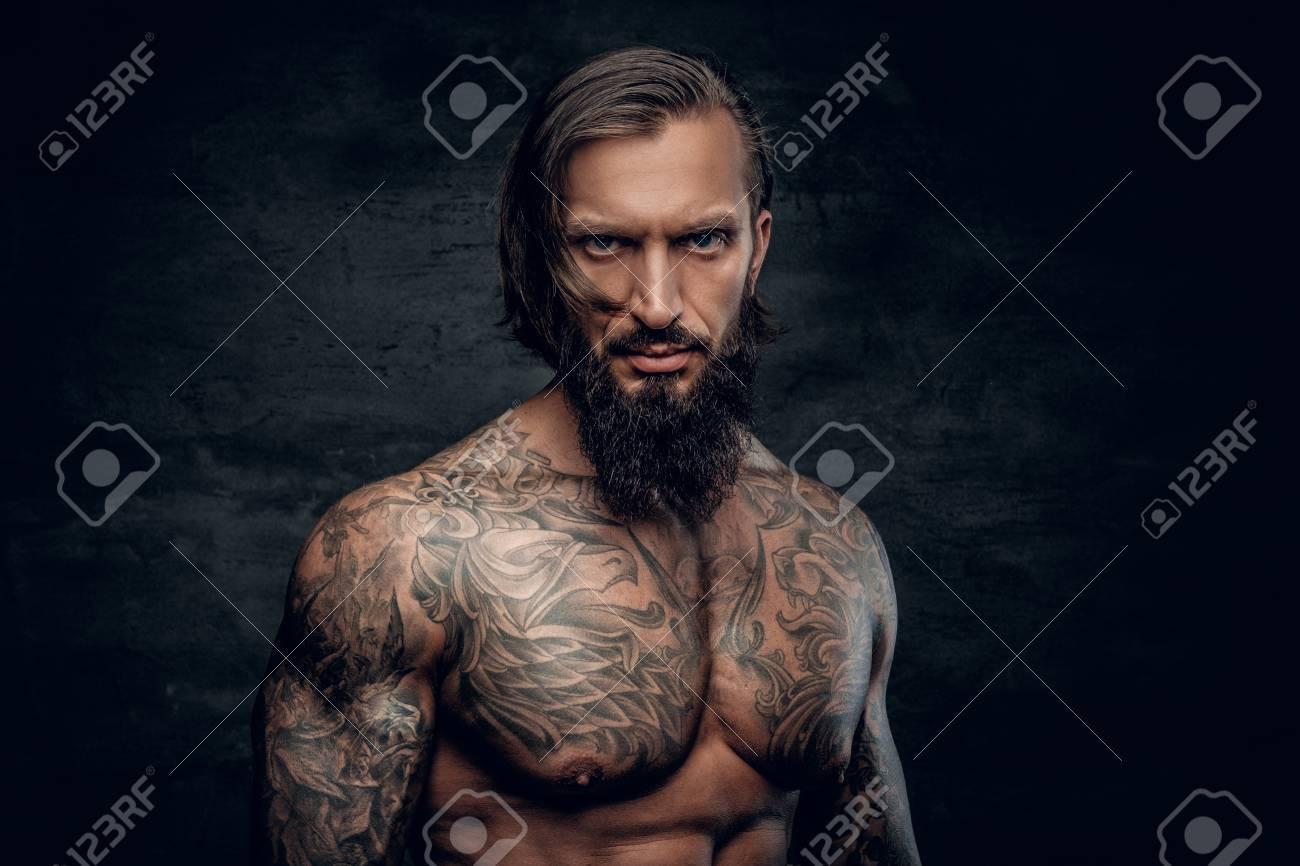 Homme Barbu Nu studio portrait d'homme barbu avec torse nu, le corps tatoué sur