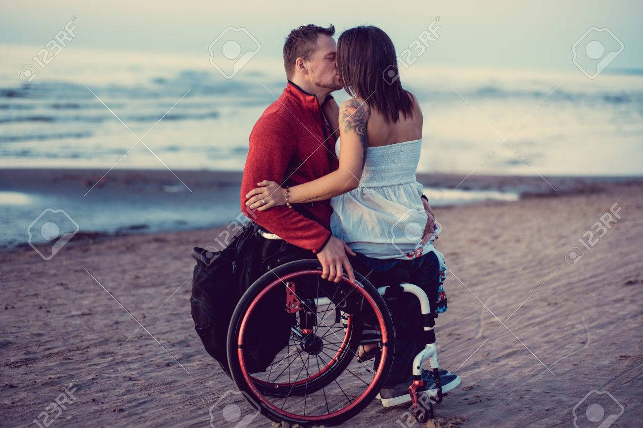 Handicapped young couple kissing on a beach. - 74800927