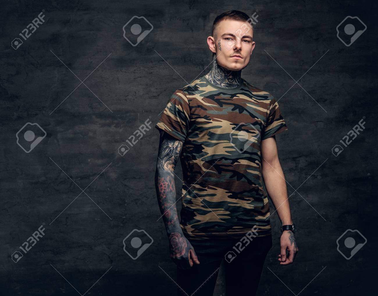 un homme avec des tatouages ??sur le cou, le visage et les bras