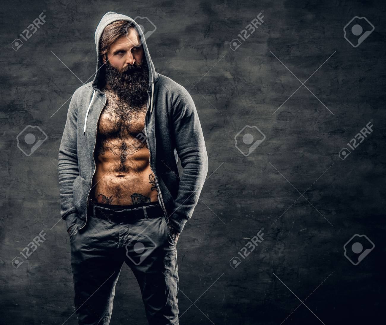Portrait of brutal bearded male with tattoo on a chest, dressed in a grey hoodie. - 75279270