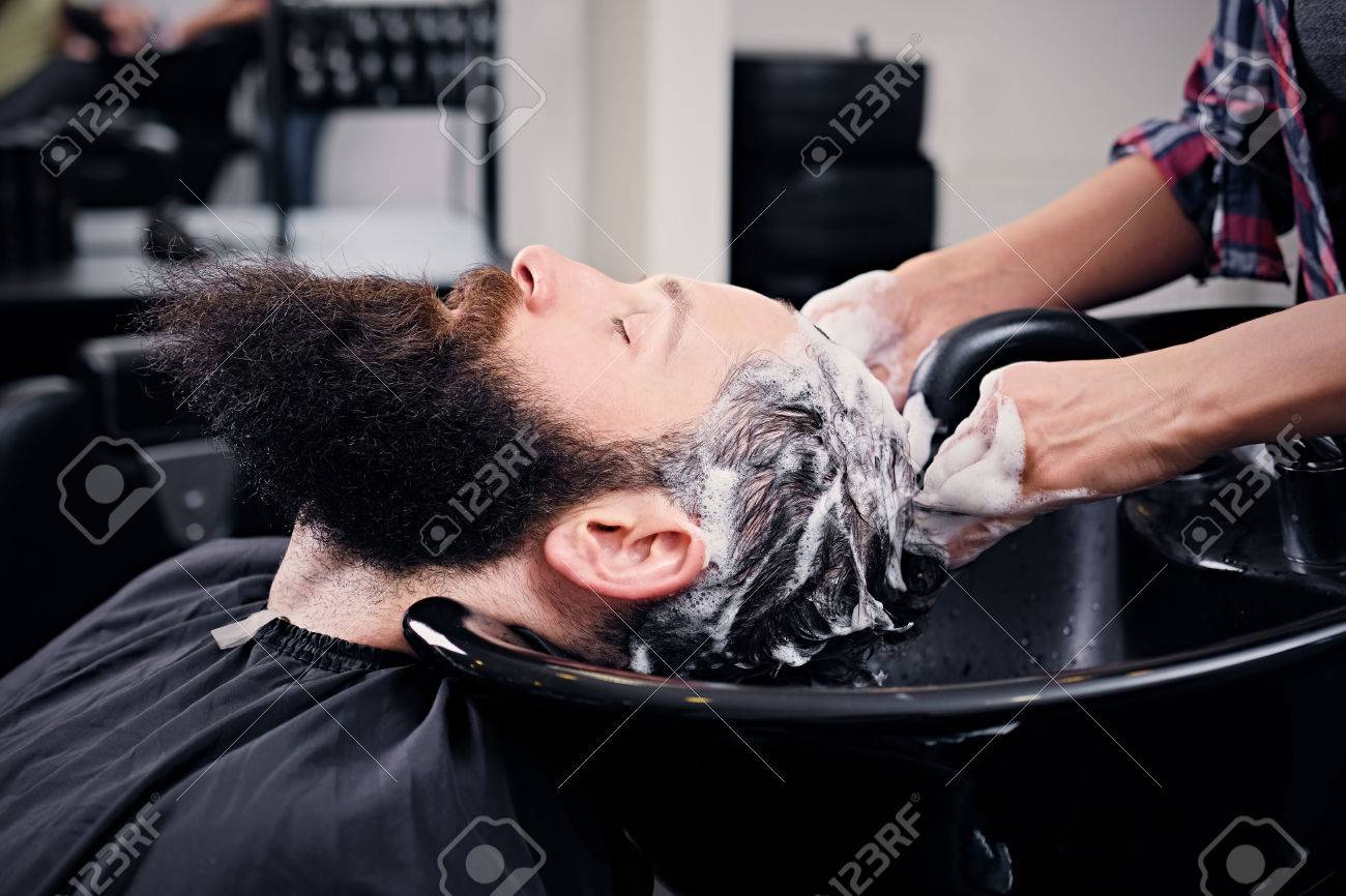 Close Up Image Of Female Hairdresser Washing Bearded Mens Hair