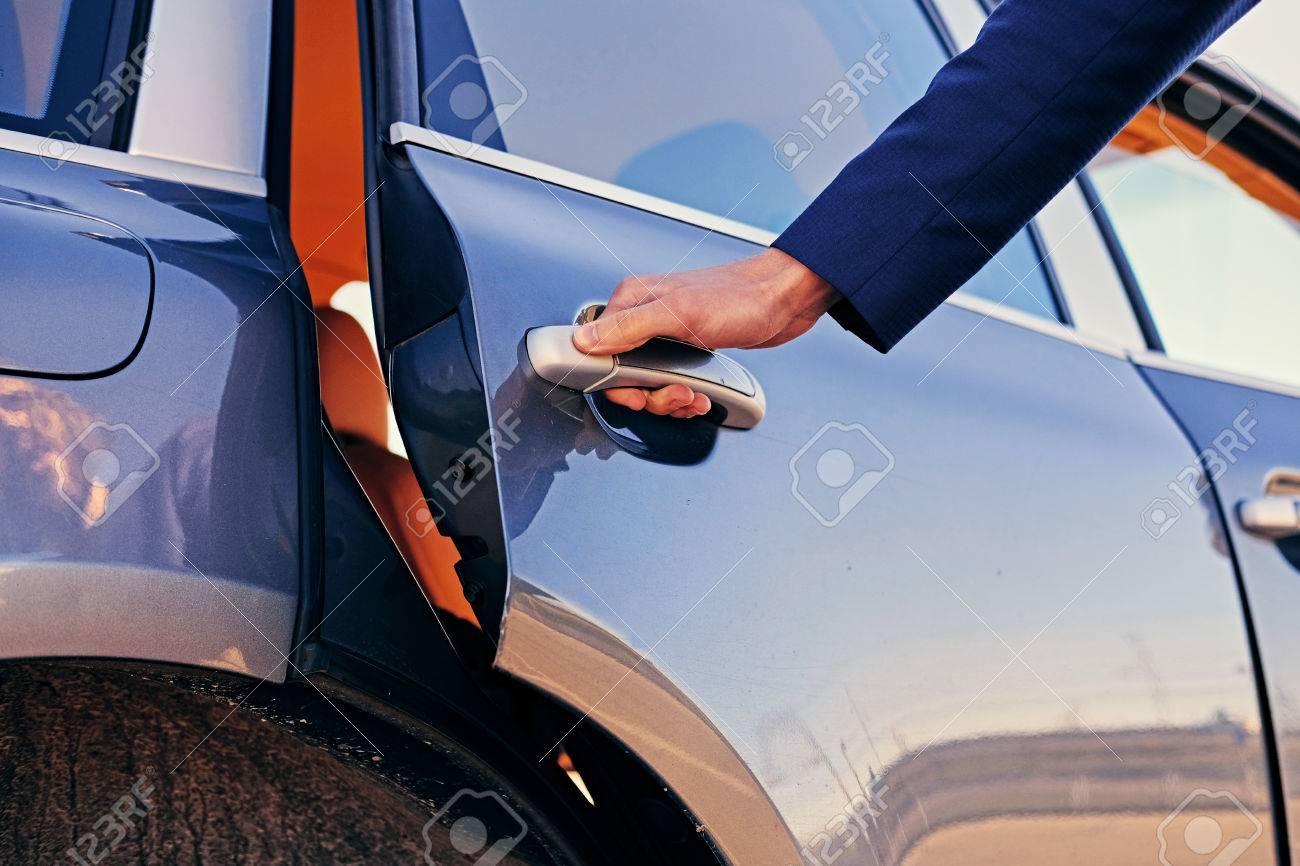 Close up image of a man opens car's door. - 84004987