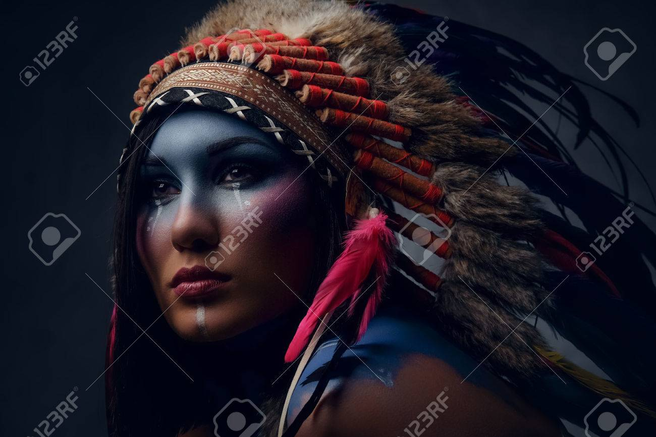 Close up portrait of shamanic female with Indian feather hat and colorful makeup. - 86446109