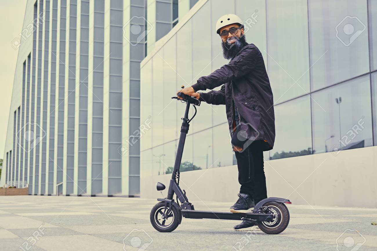 Bearded hipster male vaping and riding by electric scooter over modern building. - 86784954