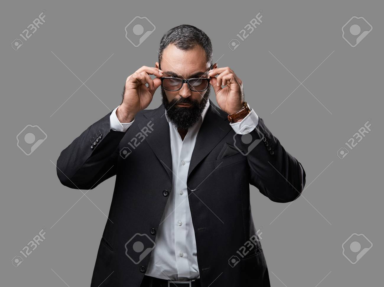 25fd5768a64f Studio portrait of bearded male dressed in a suit and sunglasses over grey  background. Stock