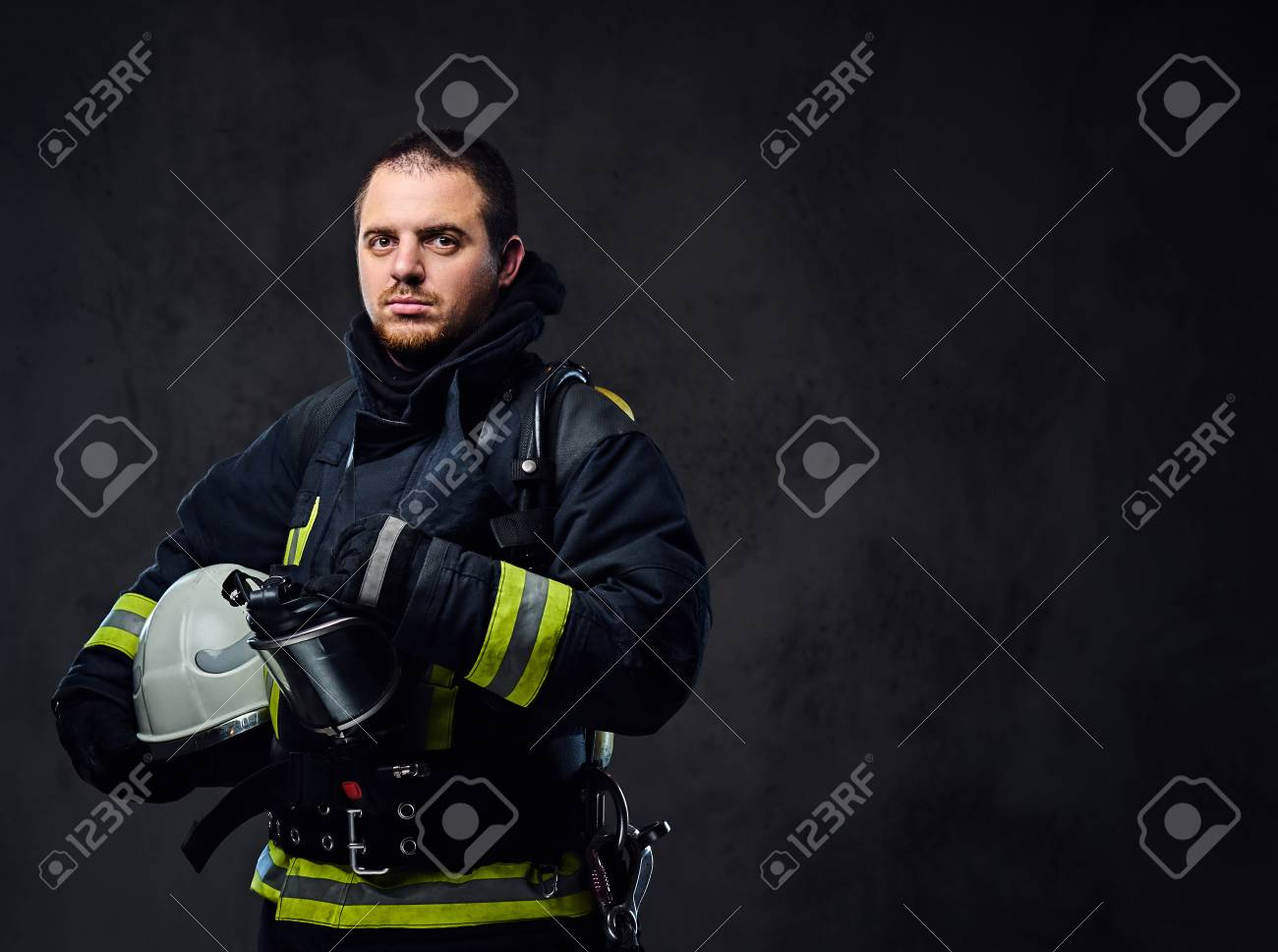 Studio portrait of firefighter dressed in uniform holds safety helmet in his arm. - 88694356