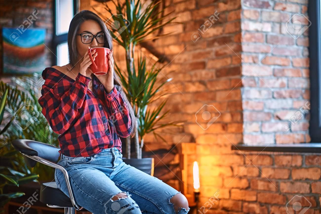 Una Mujer Morena Inconformista Vestida Con Una Camisa De Lana Y Pantalones Vaqueros Bebe Cafe En Una Habitacion Con Interior De Loft Fotos Retratos Imagenes Y Fotografia De Archivo Libres De Derecho