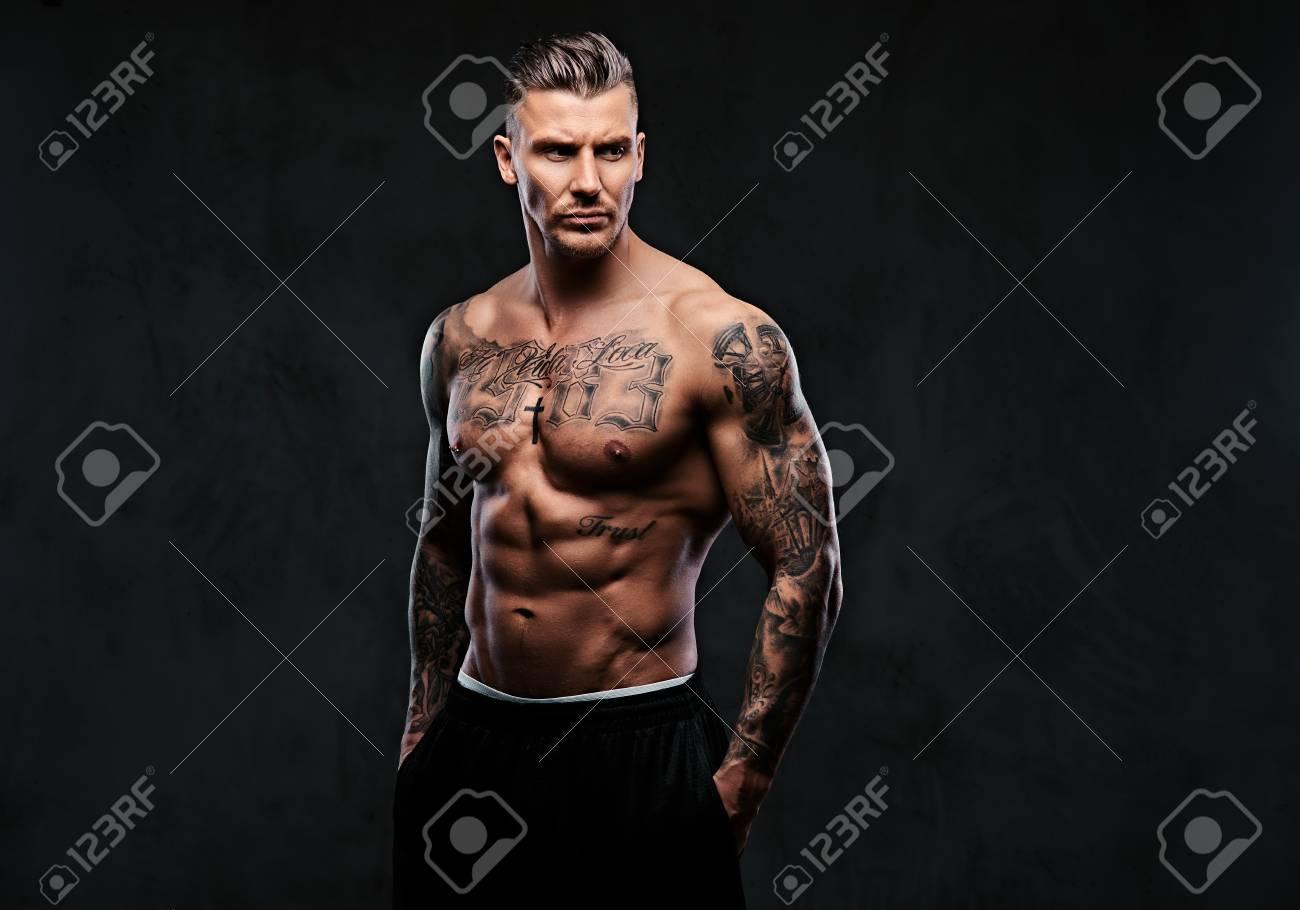 A muscular tattooed man on a dark background. - 93559352