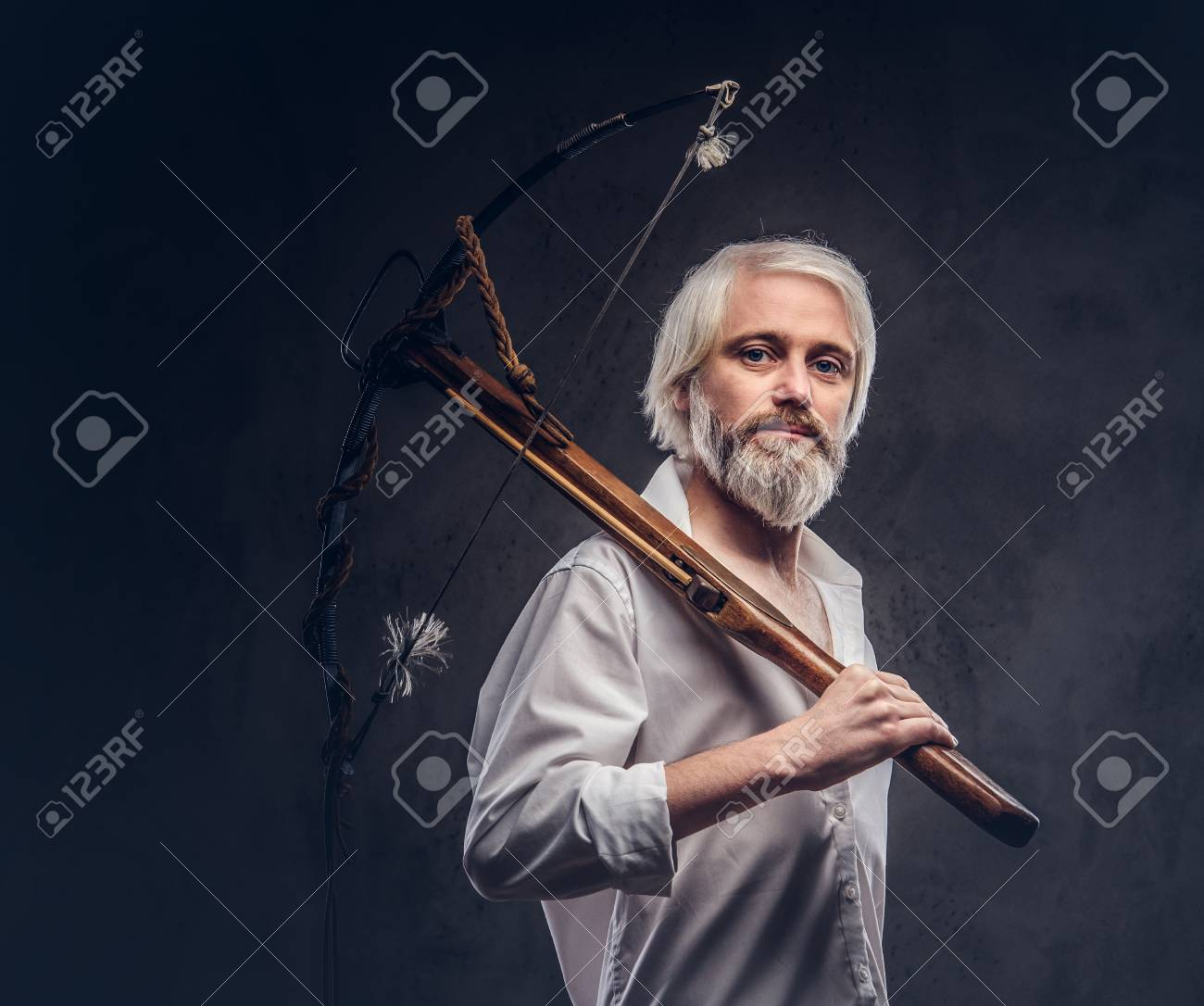 0e3bb9fb8a8 Stock Photo - Studio portrait of a smiling handsome old man with a gray  beard and white shirt holding a crossbow on shoulder.