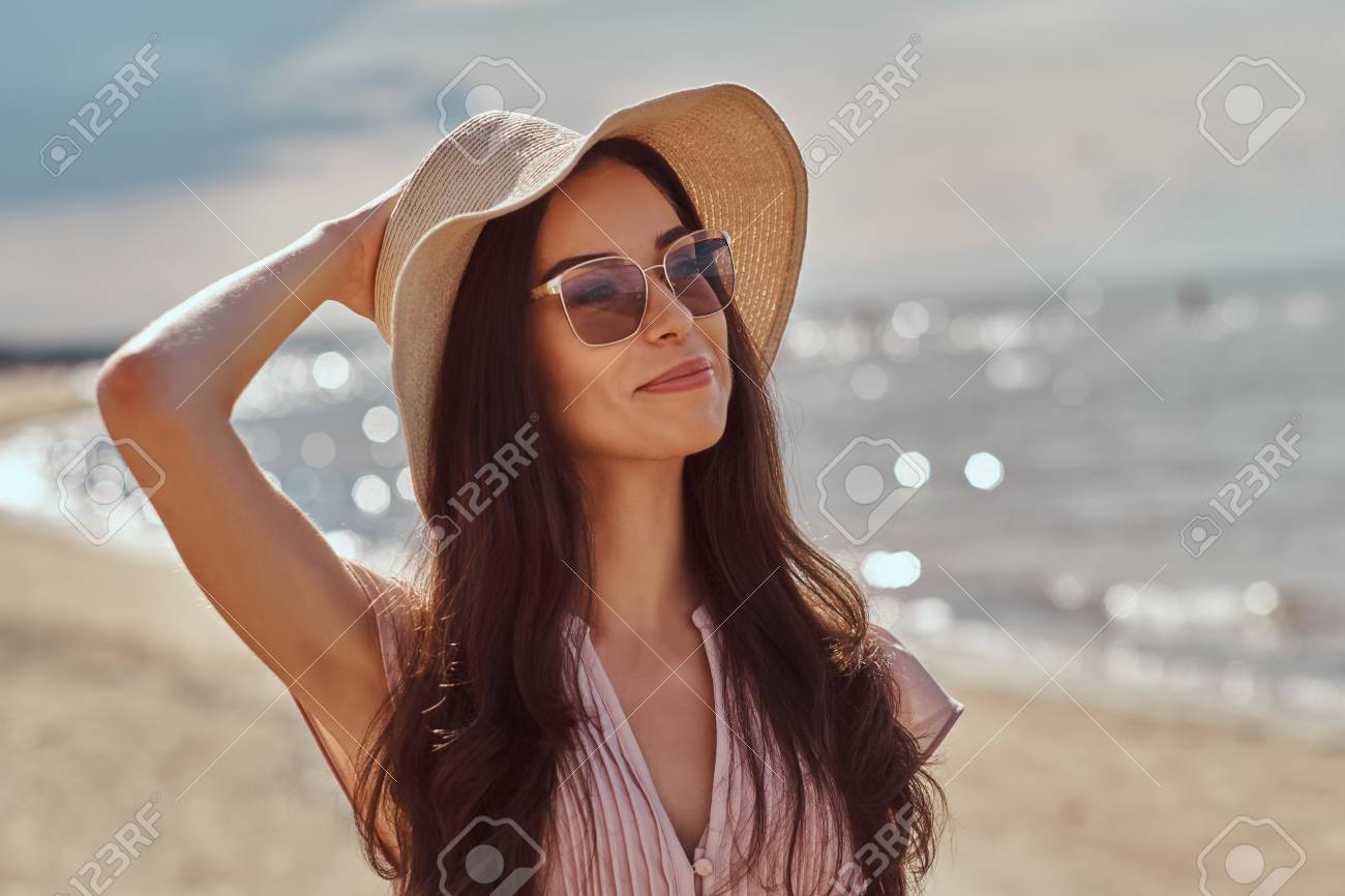 Portrait of a smiling beautiful brunette girl with long hair in sunglasses and sunglasses wearing a dress on the beach. - 106879746