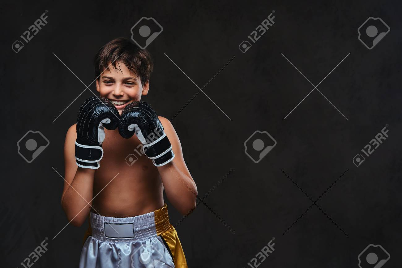 Happy handsome shirtless young boxer wearing gloves. Isolated on a dark background. - 107115293