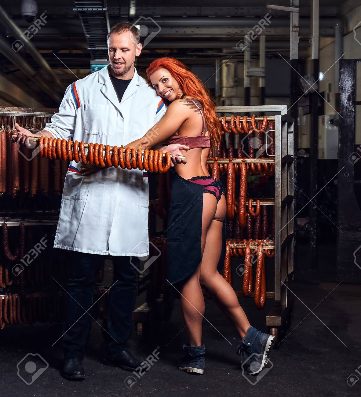 Butcher and his sexy girl assistant in the storage room. Stock Photo -  112018085