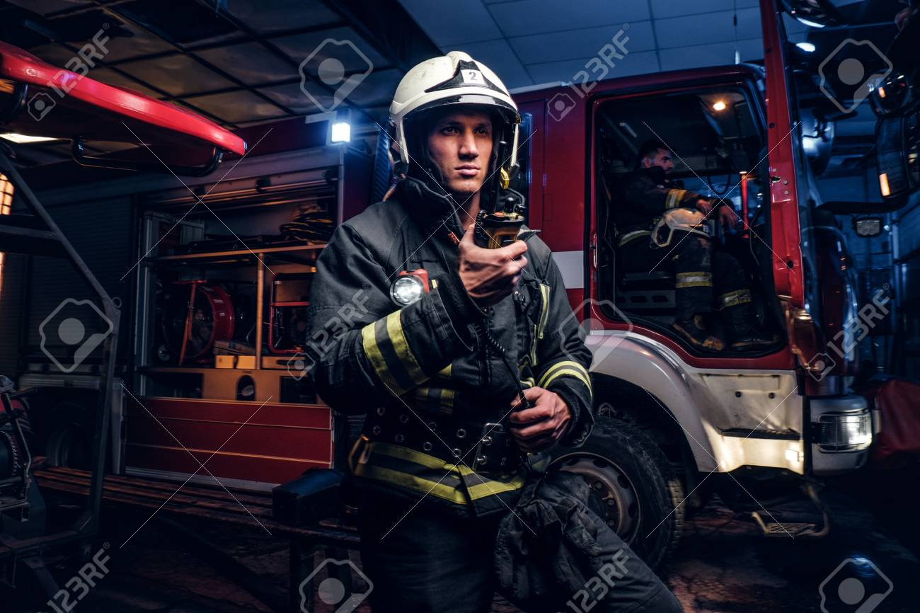 The fire brigade arrived at the night-time. Fireman in a protective uniform standing next to a fire truck and talking on the radio - 119308148