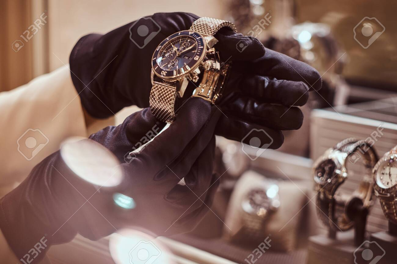 Close-up of the seller's hands in gloves shows the exclusive men's watch from the new collection in the luxury jewelry store - 119221736