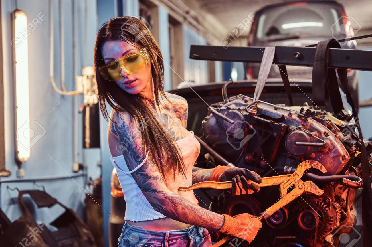 Stylish girl with tattooed body wearing protective goggles working