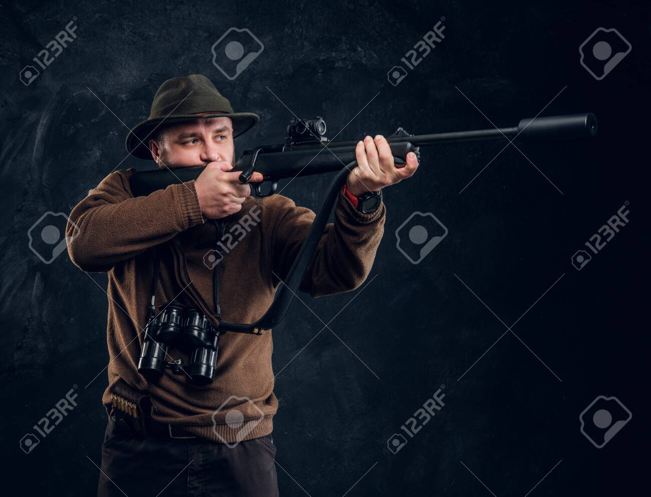 Male hunter holding a rifle and aiming at his target or prey